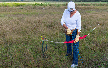 Woman In White Using Archery Supplies In Large Field - 1-20