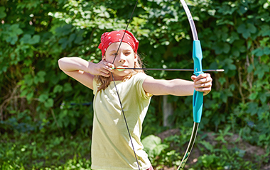 Young Girl Shooting Bow And Arrow At Target - 4-5