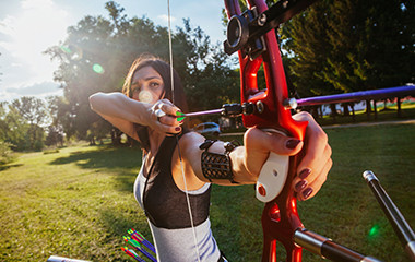 Young Woman Takes Aim with her Bow pulling the Bowstrings Tight