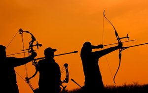Archers taking aim in front of sunset